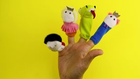 Hand with finger puppet theatre. The dragon, prince,princess and king on a yellow background stock video