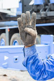 Hand and finger sign. Worker show his 4 finger in grunge cloth glove mean number four Stock Images