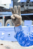 Hand and finger sign. Worker show his 3 finger in grunge cloth glove mean number three Stock Photos