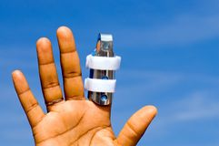Hand with finger in splint Royalty Free Stock Photography