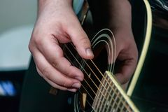 Hand fingerpicking strings of guitar. Hand fingerpicking strings of a black acoustic guitar royalty free stock photo
