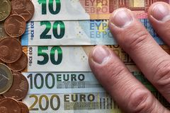 Hand fingers on background of neatly arranged stack of euro banknotes, currency bills worth ten, twenty, one and two hundred euro stock photos