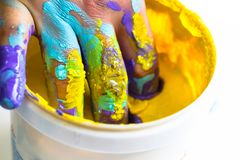 Hand and fingers dipped in yellow paint bucket. As home handmade artist and decorater painter concept, hobby home work color decoration background Royalty Free Stock Image