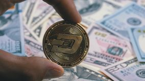 Hand in fingers holds a gold coin dash on a background with bills of dollars. Are rotating. Cryptocurrency in macro. Crypto Currency Close-up. Virtual currency stock footage