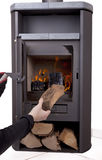 Hand firing modern wood burning stove Stock Photos