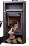 Hand firing modern wood burning stove Stock Photos