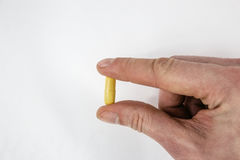 Hand with fish oil capsule  on white. Hand with tablet, drug, capsule  on white Royalty Free Stock Photos