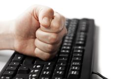 Hand fist on computer keyboard stock photo