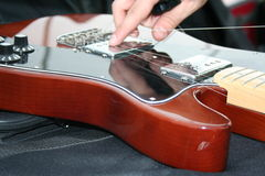 Hand Fixing a broken guitar. There is an hand that is fixing a professional guitar with all its chords broken Stock Photography