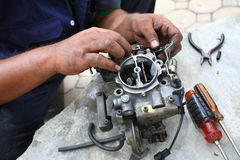 Hand fixing car engine, caburator. Stock Images