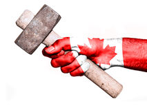 Hand with flag of Canada handling a heavy hammer. National flag of Canada overprinted the hand of a man handling a heavy hammer isolated on a white background royalty free stock images