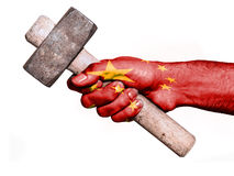 Hand with flag of China handling a heavy hammer. National flag of China overprinted the hand of a man handling a heavy hammer isolated on a white background stock photos