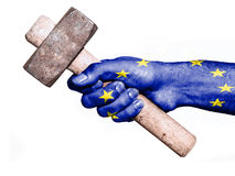 Hand with flag of European Union handling a heavy hammer. National flag of European Union overprinted the hand of a man handling a heavy hammer isolated on a royalty free stock photography