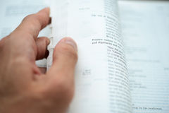 Hand flipping the bible pages with shallow DOF Stock Photo