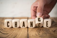 Hand flipping one of six cubes, turning the word `change ` to `chance `. On wooden background royalty free stock photo
