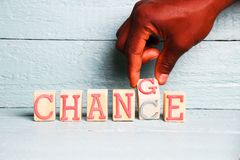 A hand flips a wooden cube with the words change into the word chance. An innovative background picture Royalty Free Stock Image