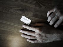 Hand on floor with help note. Darkness filtered Royalty Free Stock Photography