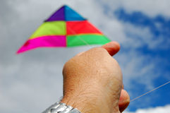 Hand flying a kite. In a cloudy sky Royalty Free Stock Photography