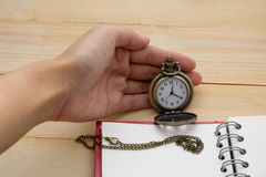 Hand fo woman holding pocket watch and notebook on wooden backgr Stock Image