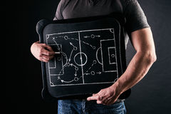Hand of a football or soccer play coach drawing a tactics of football game with white chalk on blackboard at changing room during Royalty Free Stock Images