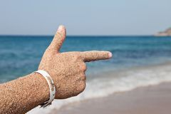 Hand forefinger pointing sea beach. Summer vacations - woman hand index finger pointing direction to sea beach Royalty Free Stock Photos