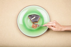 Hand with fork taking piece of chocolate cake on green dish Stock Photography