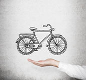 A hand in formal white shirt holds a model of a sketched bicycle. Concrete wall on background. A concept of commuting or travellin Royalty Free Stock Images
