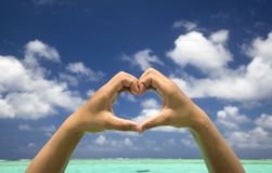 Hand forming a heart on beach Stock Image