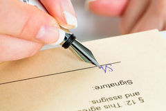 Hand with fountain pen signing contract Stock Photo