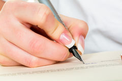 Hand with fountain pen writes under contract Royalty Free Stock Photos