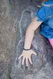 Little girl hand placed on mold of arm in stone Royalty Free Stock Images