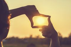 Hand framing view distant. Over sunset stock photos