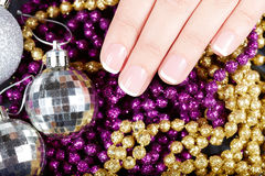 Hand with french manicured nails and Christmas decorations Royalty Free Stock Photos