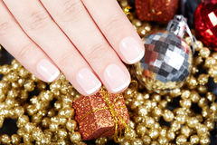 Hand with french manicured nails and Christmas decorations Stock Photo