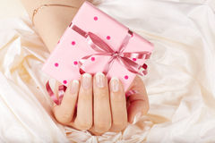 Hand with french manicured nails holding a gift box Royalty Free Stock Images