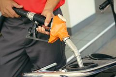 Hand fueling fuel with motorcycle Royalty Free Stock Photography