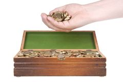 Hand full of coins over a treasure chest. Hand full of coins over an old  treasure chest Stock Photo