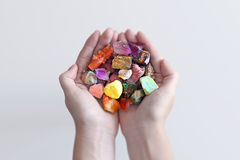 A hand full of minerals and gemstones. Photograph of a a hand holding gemstones, diamonds and minerals with lots of colors Stock Image