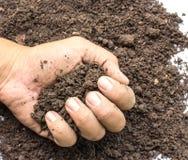 Hand full of soil against white background Stock Photos