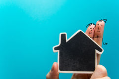 Hand with funny fingers holding white paper house figure on blue background. Real Estate Concept. Copy space top view. royalty free stock photo