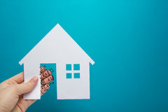 Hand with funny fingers holding white paper house figure on blue background. Real Estate Concept. Copy space top view. Stock Image
