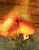 Hand of gambler rolling dice. Hand of gambler rolling gold dice with stock market paper and five dollar bill in background Royalty Free Stock Images