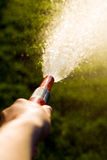 Hand with garden hose Royalty Free Stock Image