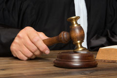 Hand with gavel. Hand of a judge holding a hammer or gavel stock image