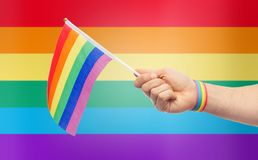 Hand with gay pride rainbow flag and wristband. Lgbt, same-sex relationships and homosexual concept - close up of male hand wearing gay pride awareness wristband Royalty Free Stock Photos