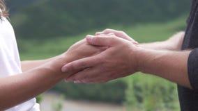 Hand in Hand gegen den Hintergrund von Bergen stock footage