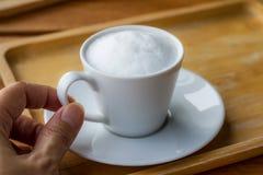 Hand - gehouden koffiekop met melkschuim en geplaatst op een houten lijst royalty-vrije stock afbeeldingen
