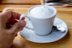 Hand - gehouden koffiekop met melkschuim en geplaatst op een houten lijst stock afbeeldingen