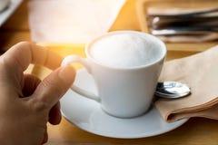 Hand - gehouden koffiekop met melkschuim en geplaatst op een houten lijst Geel licht royalty-vrije stock afbeelding