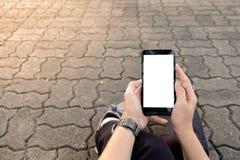 Hand genom att använda den stads- gatan för mobiltelefon royaltyfria bilder